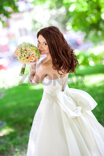the beautiful smiling bride with long flowing hair in magnificent white wedding dress with a big bow holding a flowers bouquet in her hands on a green nature sunny background.
