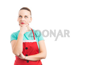 Woman wearing red Christmas apron thinking