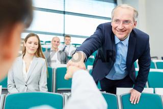 Älterer Mann begrüßt junge Kollegin mit Faustgruß