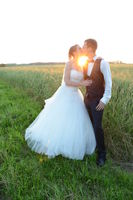 Just married jung couple standing in field and kissing each other