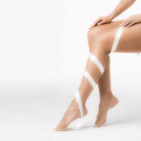 Women's legs with white ribbon