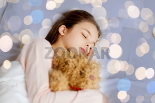 girl sleeping with teddy bear toy in bed