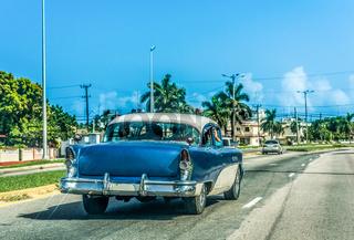 HDR- Blauer amerikanischer Oldtimer mit weissem Dach fährt durch Varadero Kuba