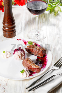 Duck breast with cherry pomegranate sauce on white plate. wooden background.