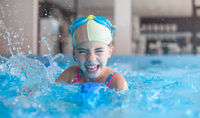 Young Girl Splashing Swimming Pool