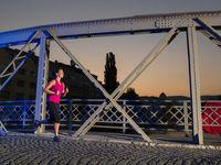 woman jogging across the bridge in the city
