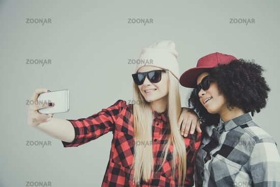 Studio lifestyle portrait of two best friends hipster girls going crazy and make selfie and have a great time together. Isolated on white background.