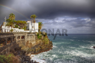 Town city hall over rocks and sea waves under a rainbow