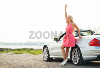 happy young woman in convertible car waving hand