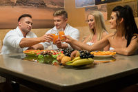Happy young couples by table in sauna rest room