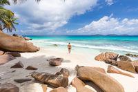 Man enjoying Anse Patates picture perfect beach on La Digue Island, Seychelles.