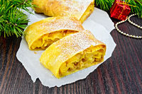 Strudel pumpkin and apple with pine branches on wooden board