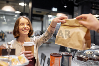 woman taking paper bag from seller at cafe