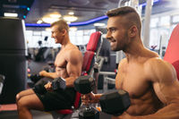Young muscular men exercising with dumbells in gym
