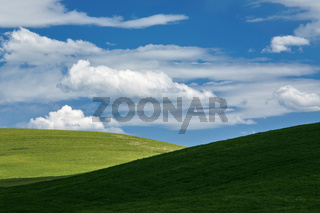 White clouds above green hills