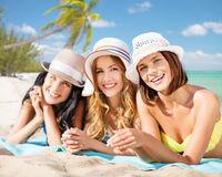 group of happy women in hats sunbathing on beach