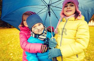 happy children with umbrella in autumn park