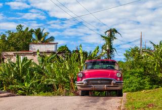 HDR - Roter amerikanischer Oldtimer parkt unter blauem Himmel im Landesinneren in Santa Clara Kuba