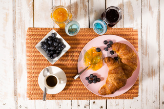 Breakfast with croissant, blueberries, coffee and jam over a tablecloth