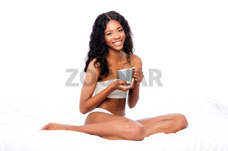 Beautiful happy woman with delicious coffee sitting in white bed