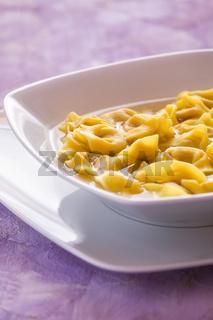 Tortellini in broth in a white plate
