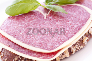 Heart-shaped salami on farmhouse bread as closeup