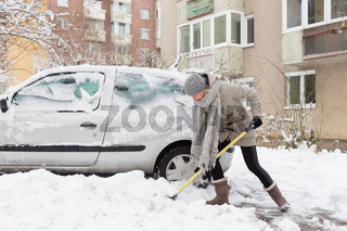 Independent woman shoveling snow in winter.