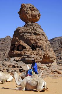 Tuareg Nomaden lagern mit ihren Dromedaren an einem Felsen im Akakus-Gebirge