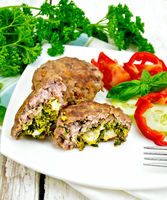 Cutlets stuffed with vegetables in plate on light board