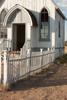 Old white church front with wooden picket fence in front