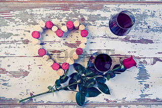 Two glasses of red wine and a heart with corks