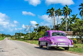 Lila farbener amerikanischer Oldtimer parkt auf dem Seitenstreifen in Santa Clara Kuba