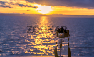 Sunset over water and a DSLR camera
