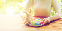 close up of woman hands with easter eggs and bunny