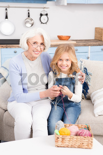 Grandmother and granddaughter knitting