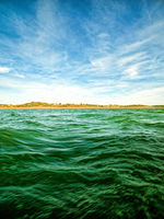 Green Ocean Waves and Blue Sky with Clouds