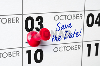 Wall calendar with a red pin - October 03