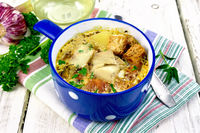 Soup fish with vegetables and croutons on light board