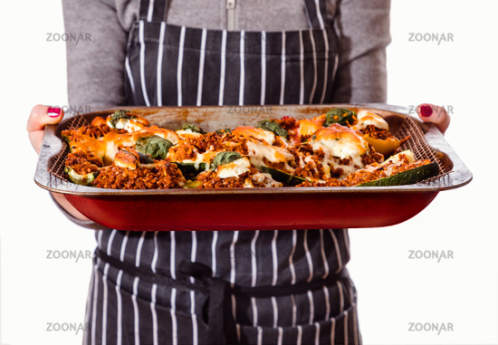 Woman in apron holding tray with mince meat stuffed peppers and courgettes, isolated on white.