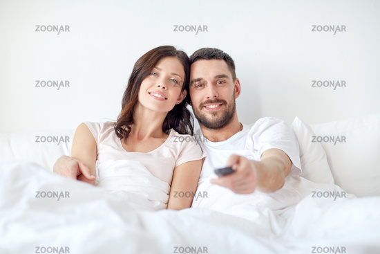 happy couple lying in bed at home and watching tv