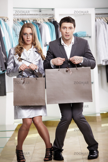 The surprised guy and the girl with packages in hands in shop