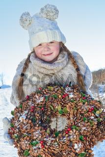Mädchen mit Zöpfen hält einen Adventskranz