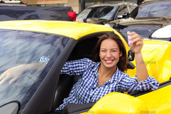 junge Frau in neuem Sportwagen zeigt Autoschlüssel