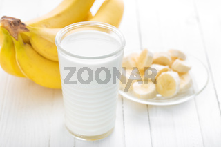 Yogurt with fresh bananas on white wooden background closeup, healthy breakfast