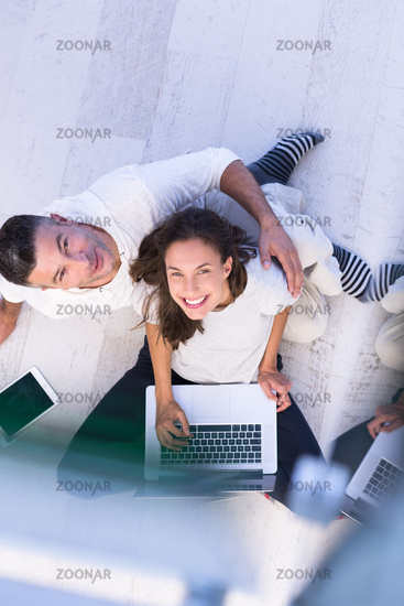 couple using tablet and laptop computers top view
