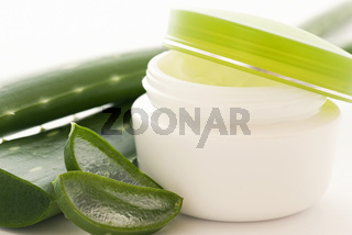 Aloe creme box with Aloe leaves and slices as closeup