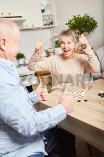 Seniorin jubelt beim Brettspiel zuhause
