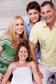 Portrait of happy family of four posing in front of camera
