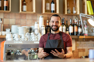 man, barman or waiter with tablet pc at bar
