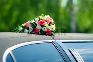 A bunch of roses on the roof of wedding car
